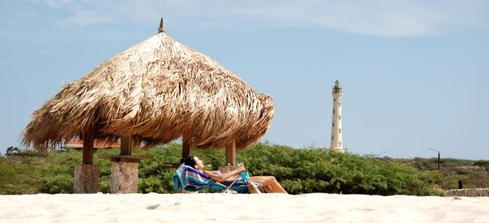 Arashi Beach - Woman is sunbathing - Lighthouse in the background