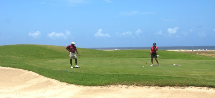 Couple playing golf at the North Coast of Aruba