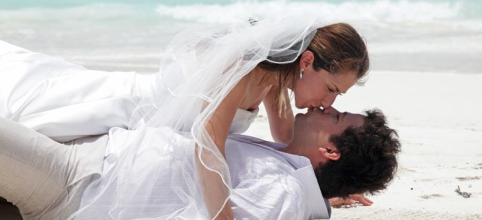 Married couple kissing each other on the beach
